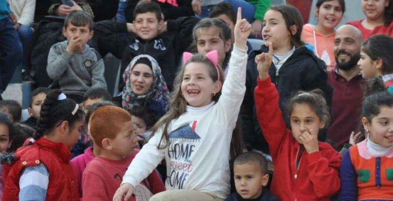 Young girl raising her hand high in front of a group of children