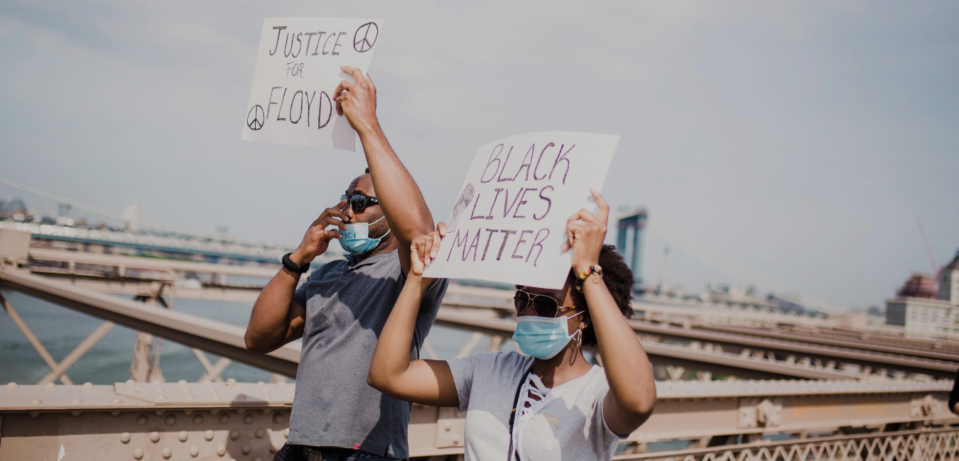 Protestors in PPE masks walk across a bridge holding signs that read: Justice for Floyd and Black Lives Matter