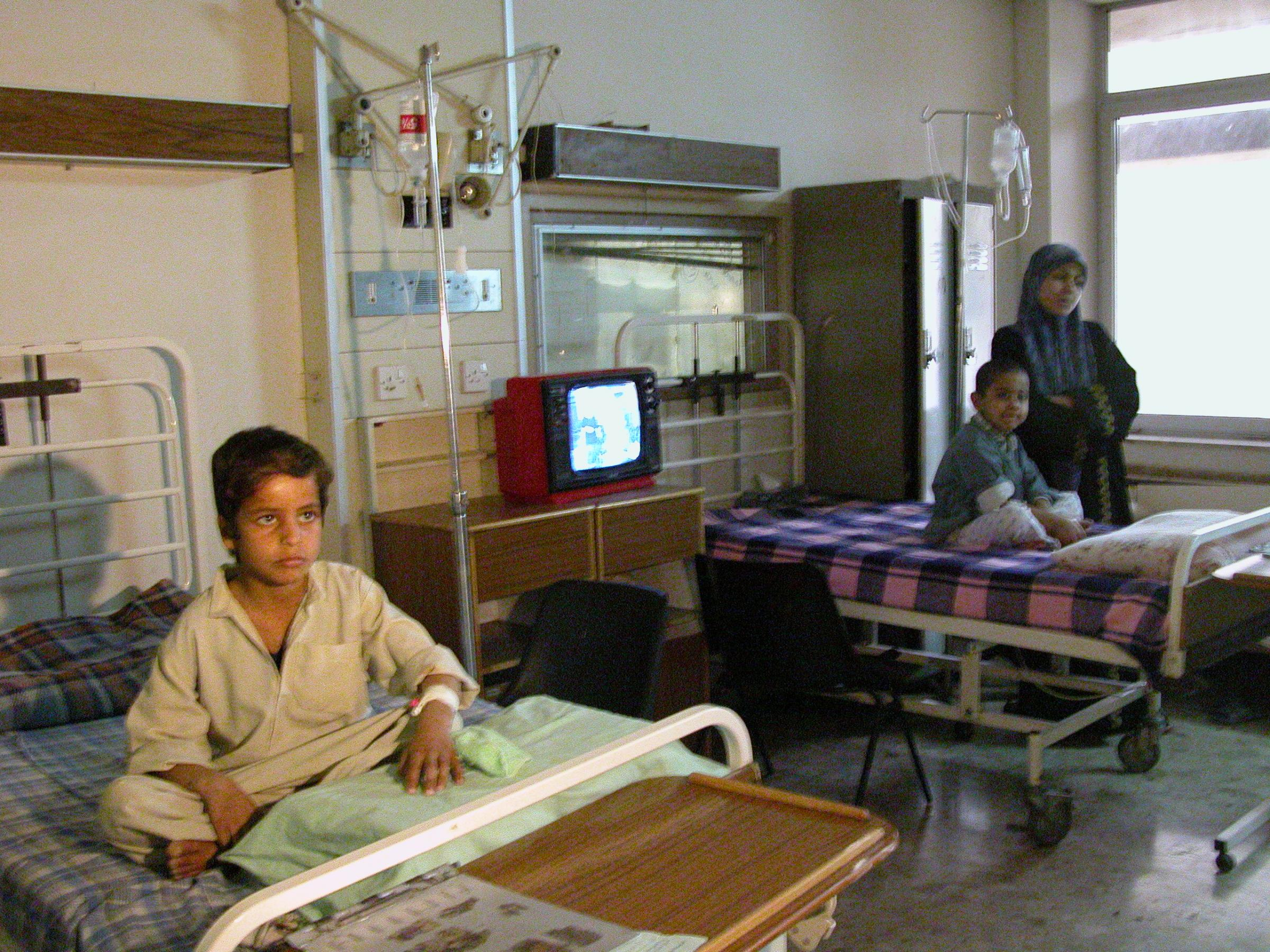 Iraqi children sitting on beds in a hospital, a mother stands with them.