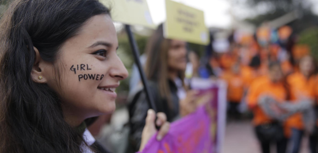 "A young girl on the left-hand side of the image smiles during a protest. ""Girl power"" is written in black paint on her cheek."