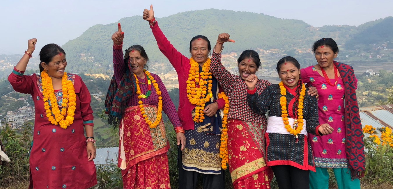 A group of Indigenous Nepali women cheer with their hands raised.