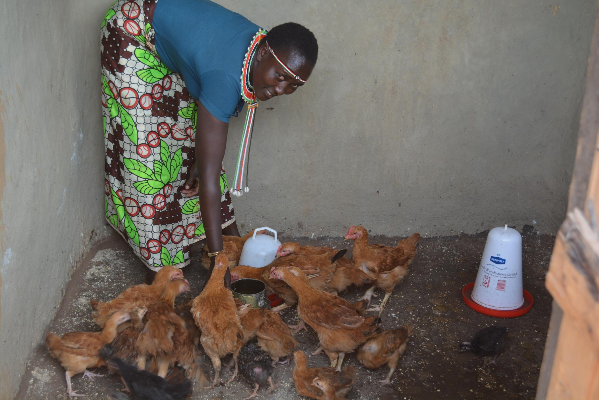 Hellen feeding her chickens in West Pokot, Kenya