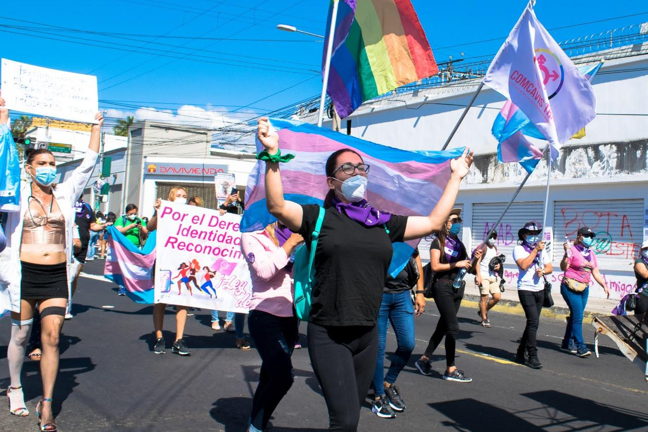 Members of Colectivo Alejandria hold up LGBTIQ+ pride and trans pride flags during a march on International Women's Day.