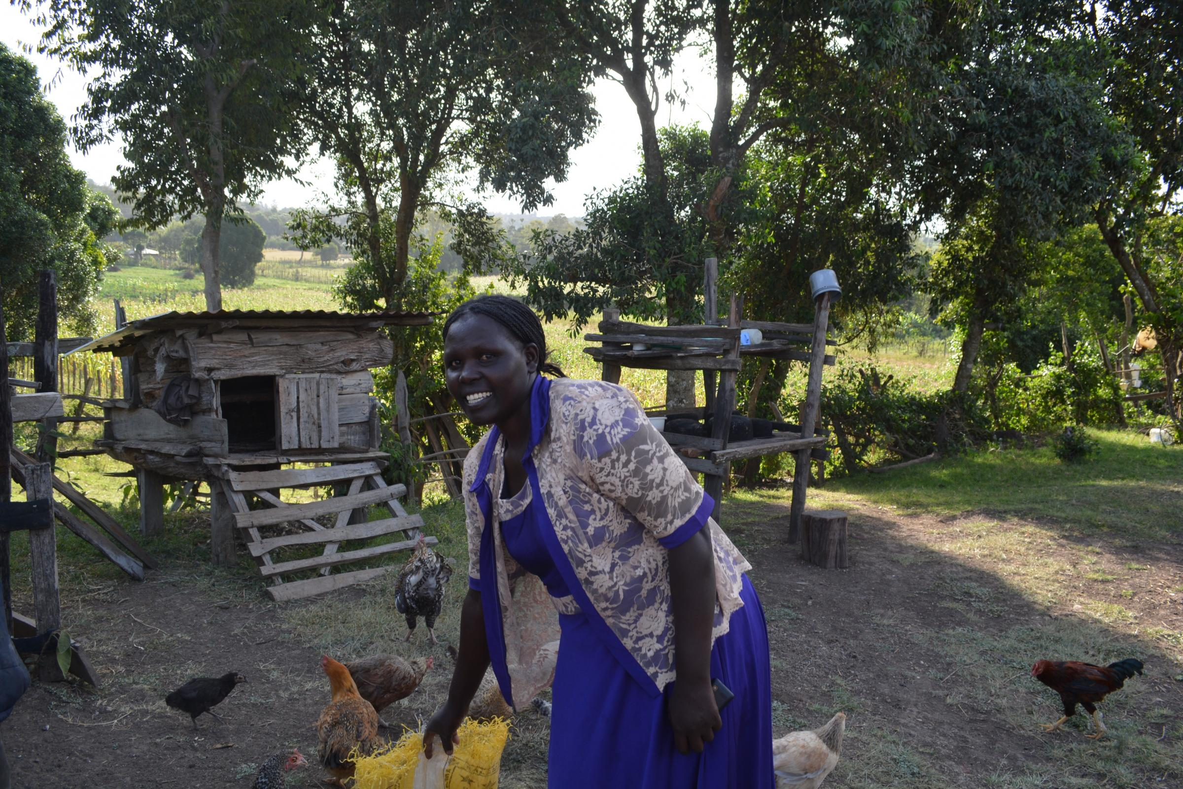 Sylvia feeding her chickens in Kenya