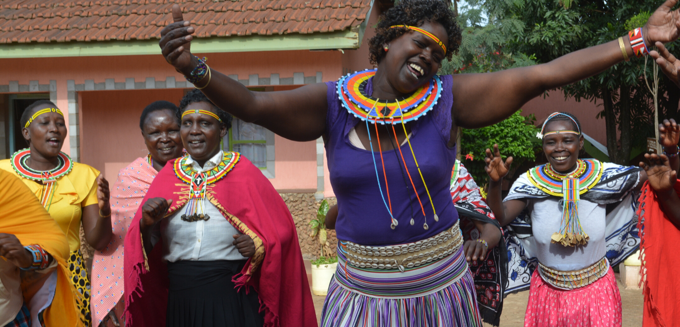 Kenyan woman dances in front of a group of women in celebration.