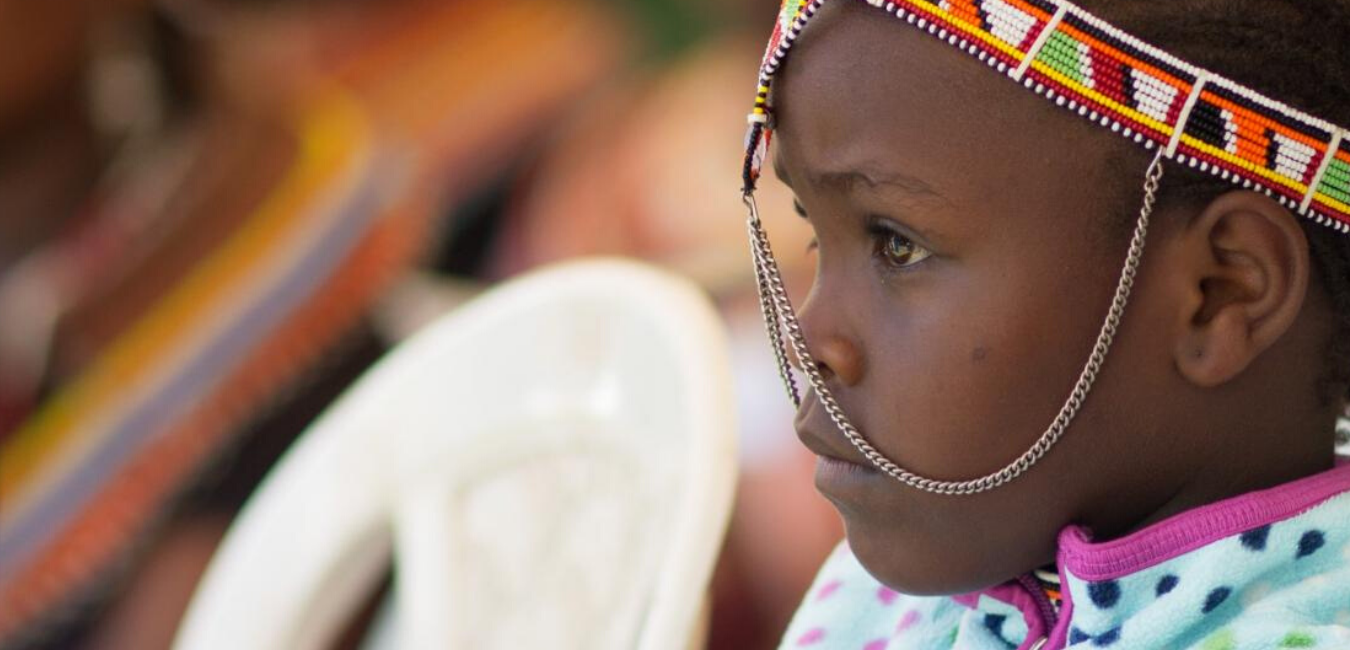 Young Kenyan girl sits with a stoic look and traditional headwear.