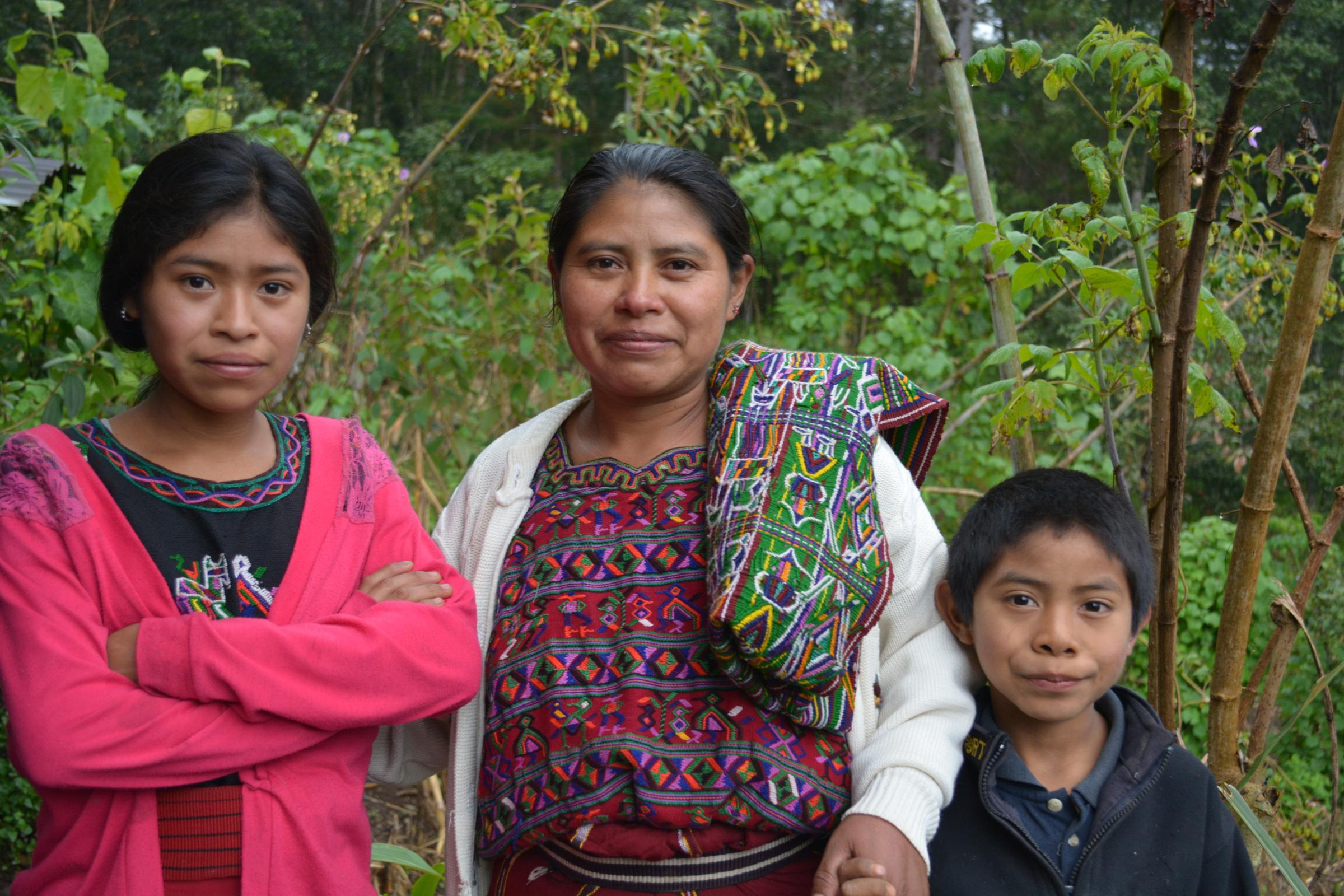 Guatemala - Woman stands with two children by her side.