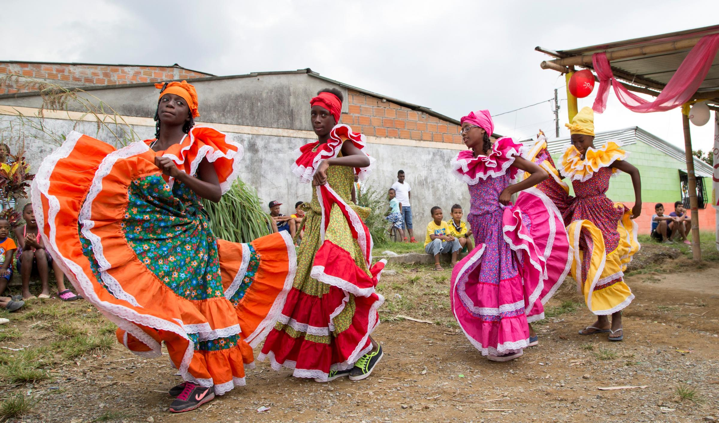 A group of young girls with colorful dresses dancing in a single file line.