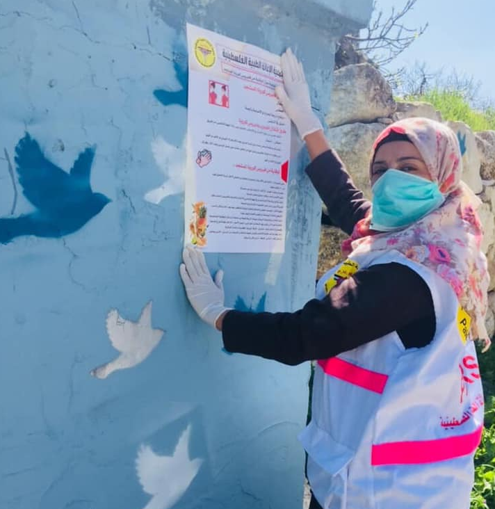 Palestinian woman puts up an informative poster.