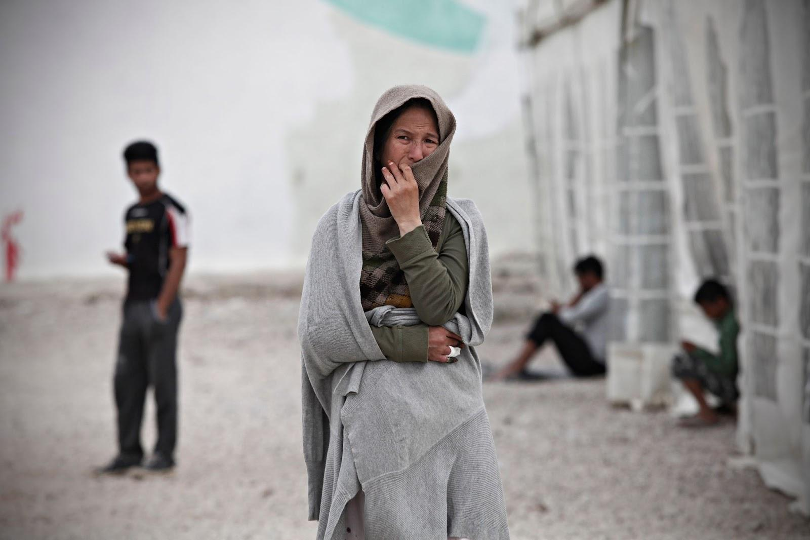 An afghan woman stands in the center of the photo holding on to her hijab. She has a sullen facial expression.