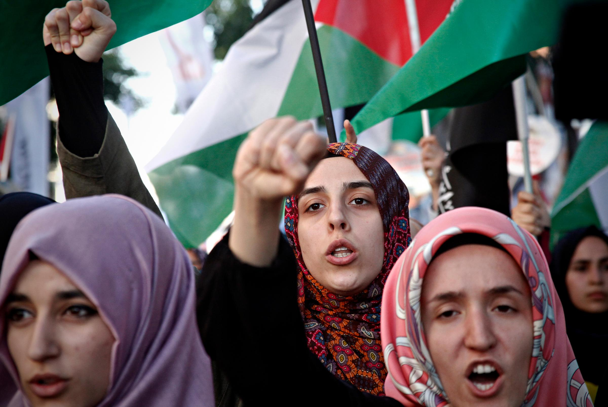 A group of women wearing hijabs gather in protest, holding up solidarity fists and standing in front of Palestinian flags
