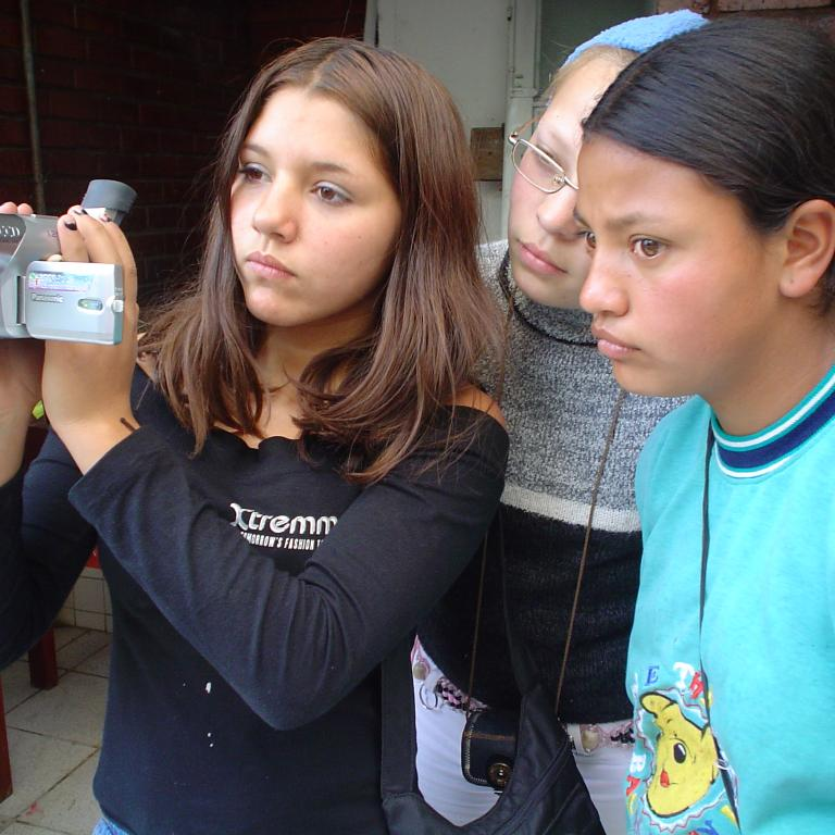 Two young girls during a videography workshop looking through video footage