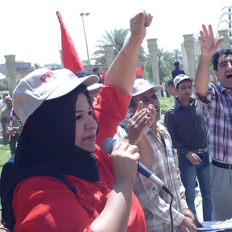 Woman speaking on a microphone with a solidarity fist up