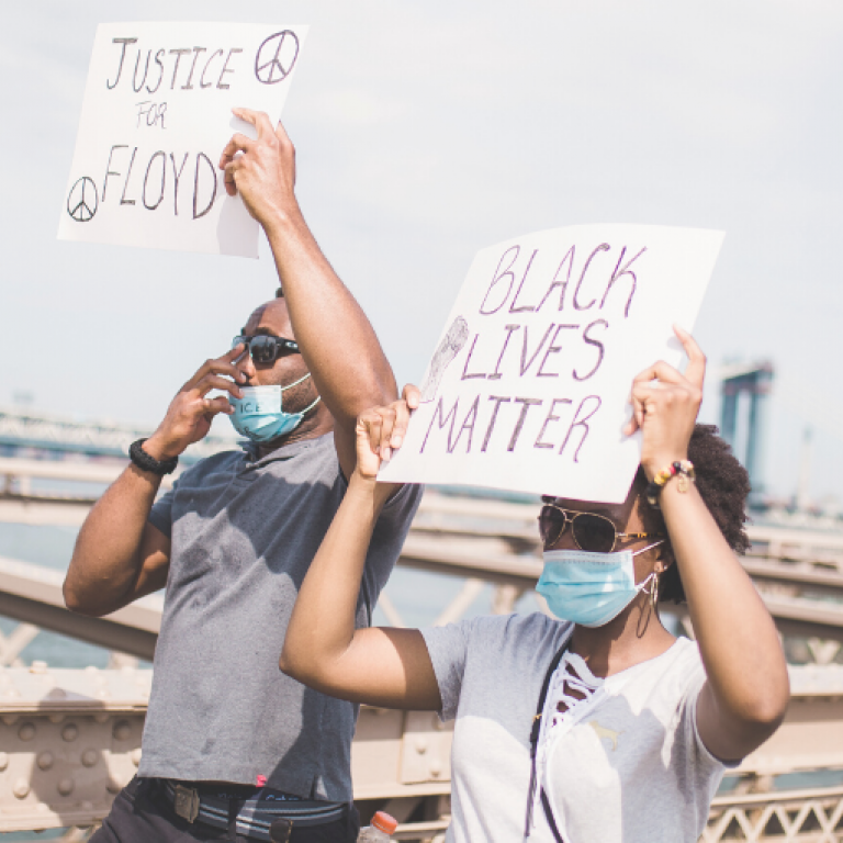 "Two Black protestors wearing PPE hold signs that read ""Black Lives Matter"" and ""Justice for Floyd"" during a protest on a bridge"
