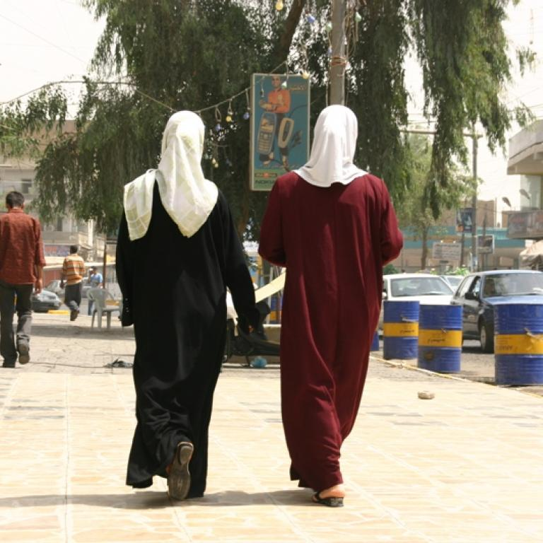 Two Iraqi women in traditional garb walk away from camera.