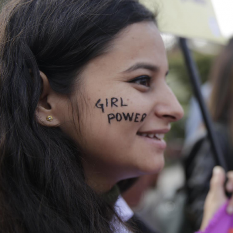 "A girl smiles at a rally. She has ""Girl Power"" written across her cheek in black paint."