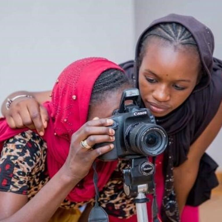 Two young girls, a part of the Mali Musso program, look through a camera during a workshop.