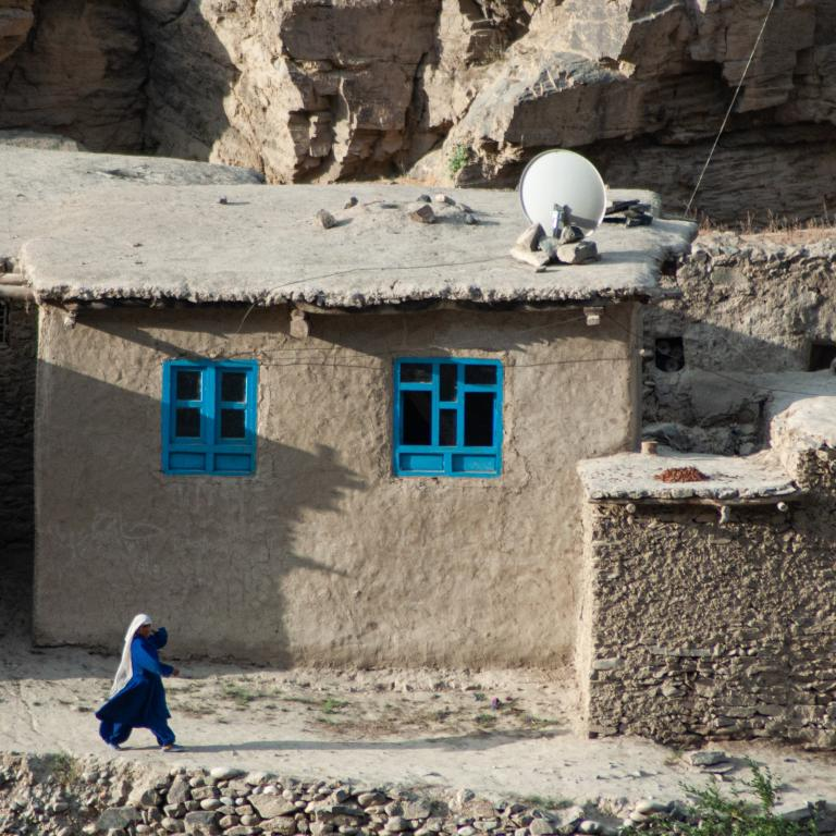 Afghan woman dressed in a blue burka walks outside of building structures.