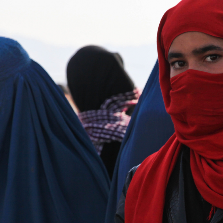 Young girl wearing a red niqab looks into the camera while in a crowd of women wearing blue burkas.