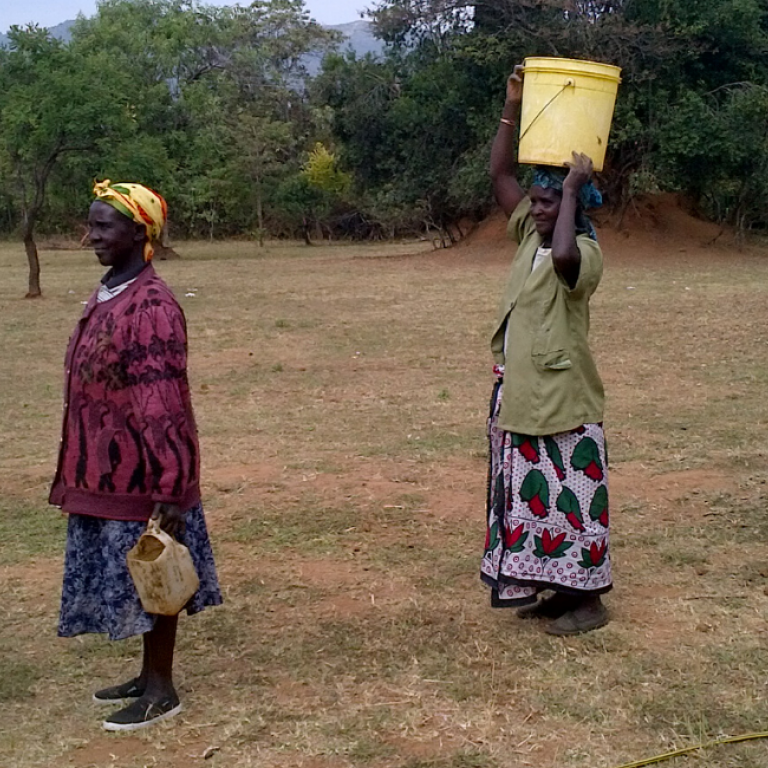 Kenyan women stand in line to collect water.