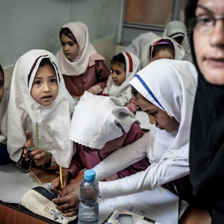 Woman and girls in hijab sit together.
