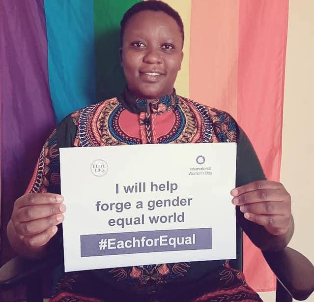 """A member of ELITE sits in front of a rainbow Pride flag with a sign that reads """"I will help forge a gender equal world. #EachforEqual"""""""