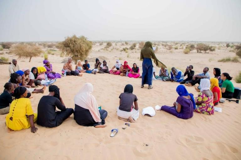 Group of young women and girls sit together in a circle on the sand of an end-of-day gathering.