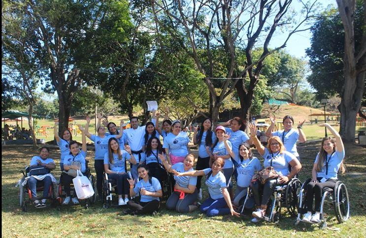 A group of people with blue shirts on, some in wheelchairs, pose for a photo - many with their hands raised to the sky in celebration.