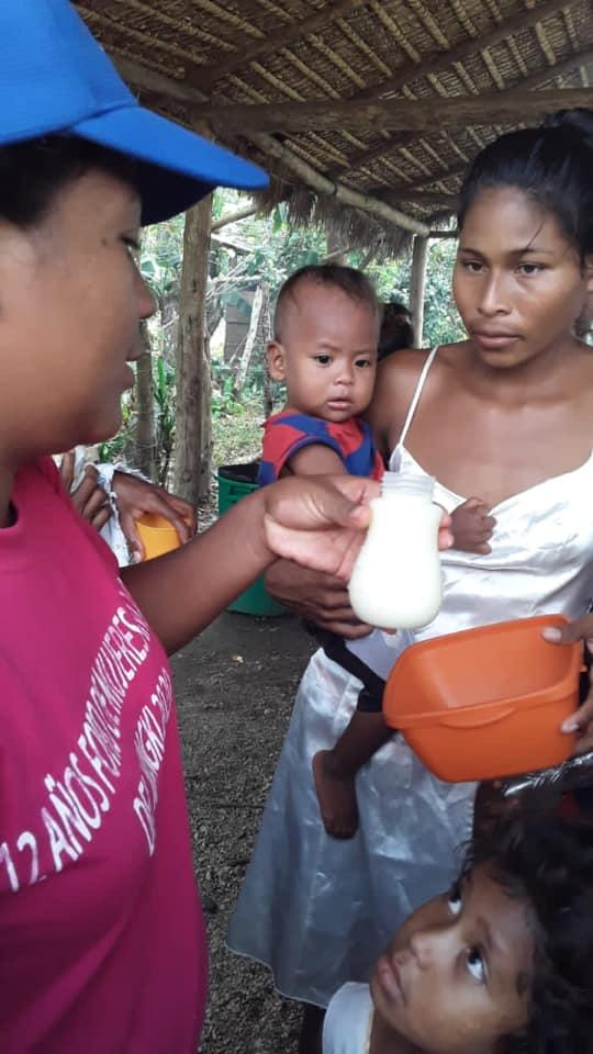 Wangki Tangni promotoras give milk to women and children in shelters.