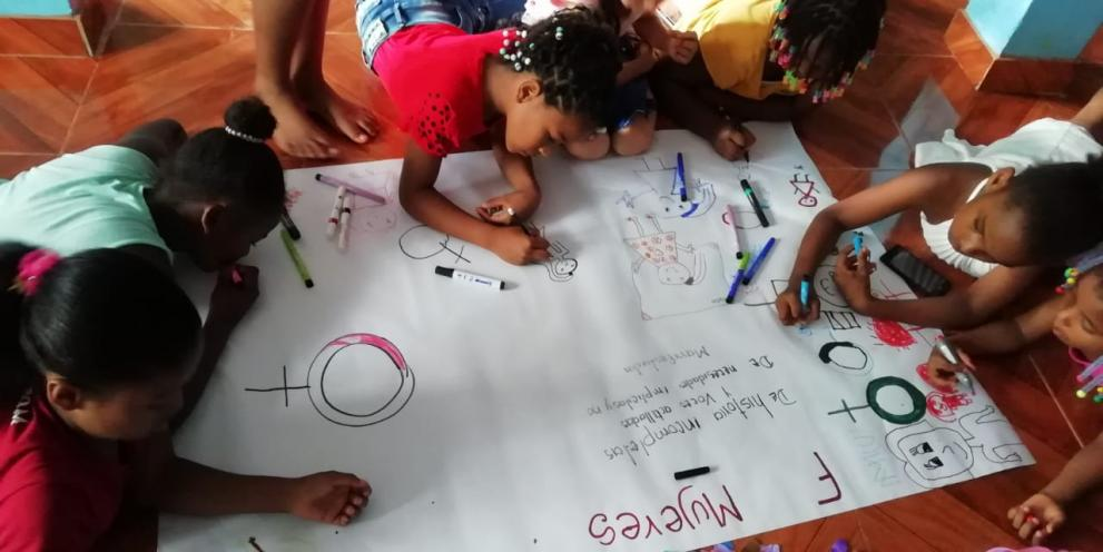 A group of children drawing together on a large sheet of paper.