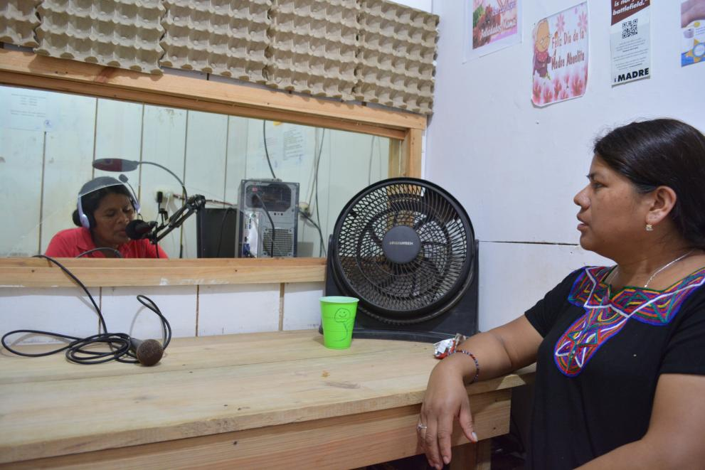 Two women sit on opposite sides during a radio interview and Wangki Tangni's radio station