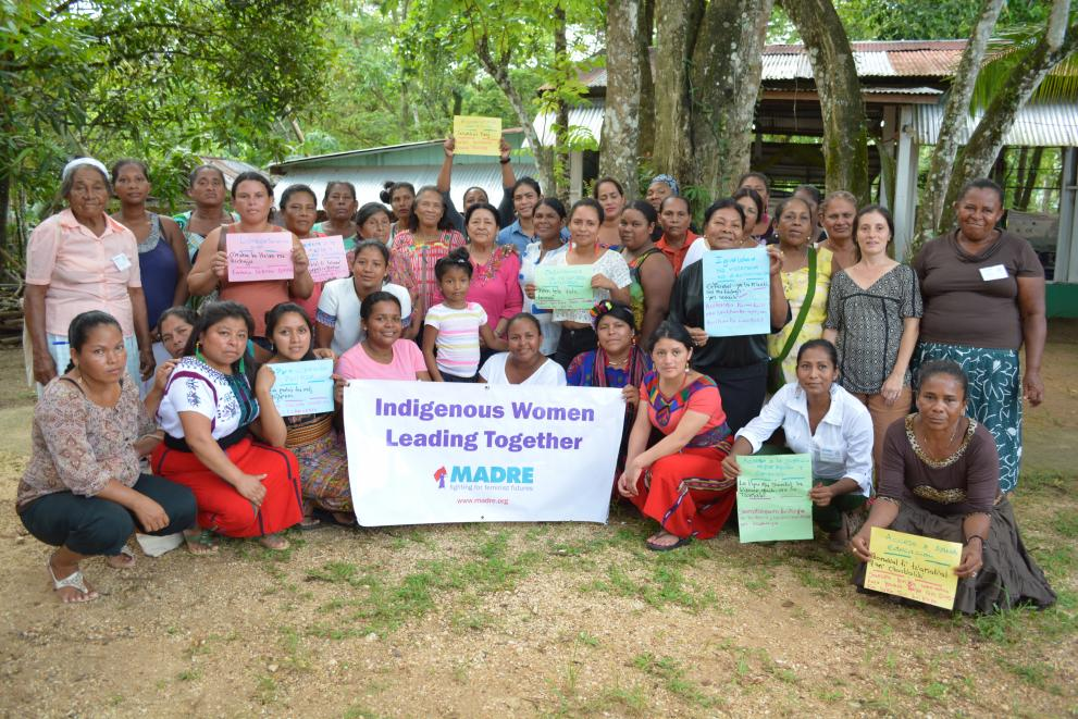 Women gather together, holding signs from a workshop activity