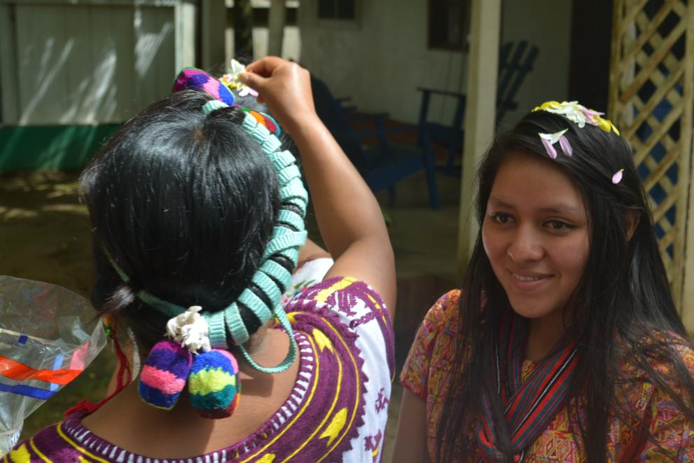 Ixil woman places flowers on top of the heads of other members of the group to prepare for a ceremony.