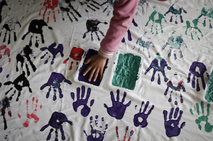 A hand rests inside a small container of purple paint, surrounded by red, purple, and green handprints on a large white sheet.