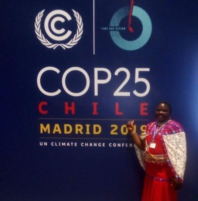 Our partner, Jolene Sempeyo Lepakuo, poses in front of a wall design with #COP25 branding.