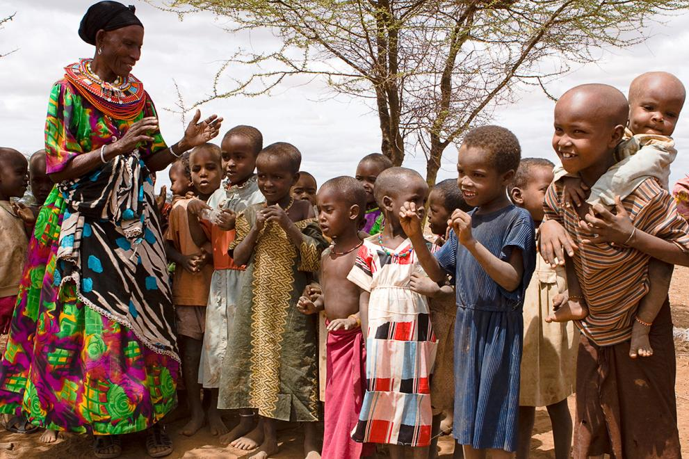 Kenyan woman in traditional dress, connects with young children.