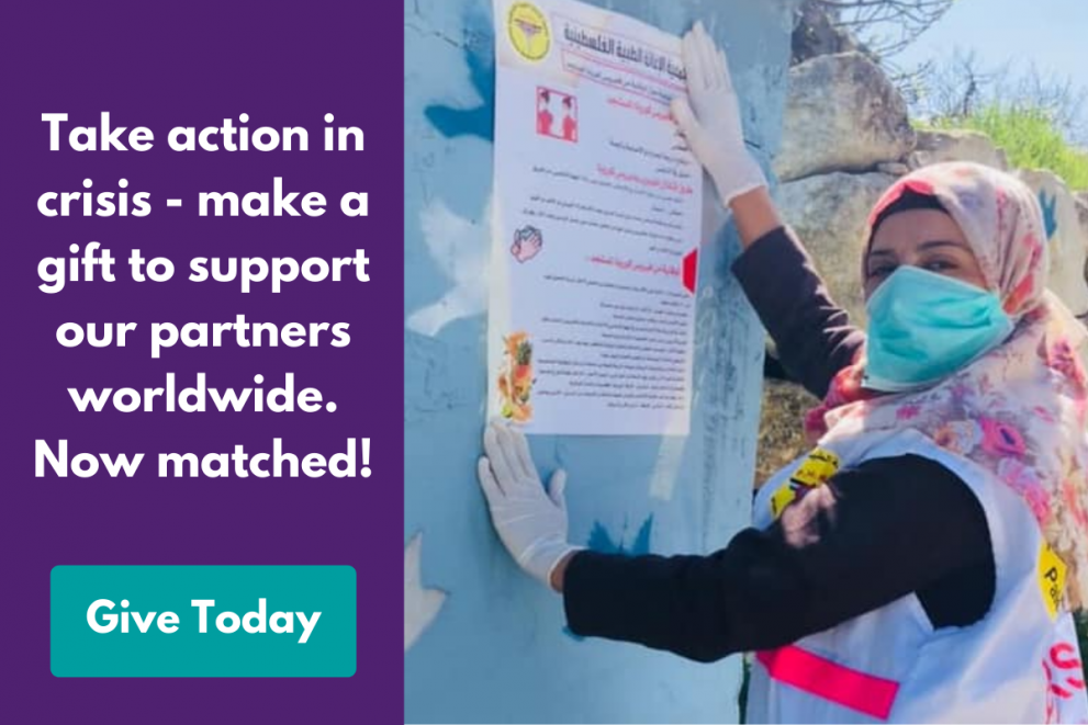 Graphic with text: A woman in PPE puts up a poster with information about COVID-19 prevention. Beside her, the text reads: Take action in crisis - make a gift to support our partners worldwide. Now matched! Give today