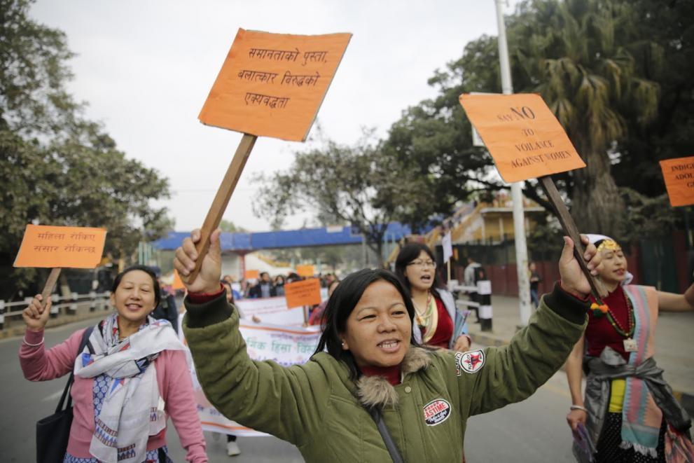 A Nepali woman chants while holding up two signs during a rally.