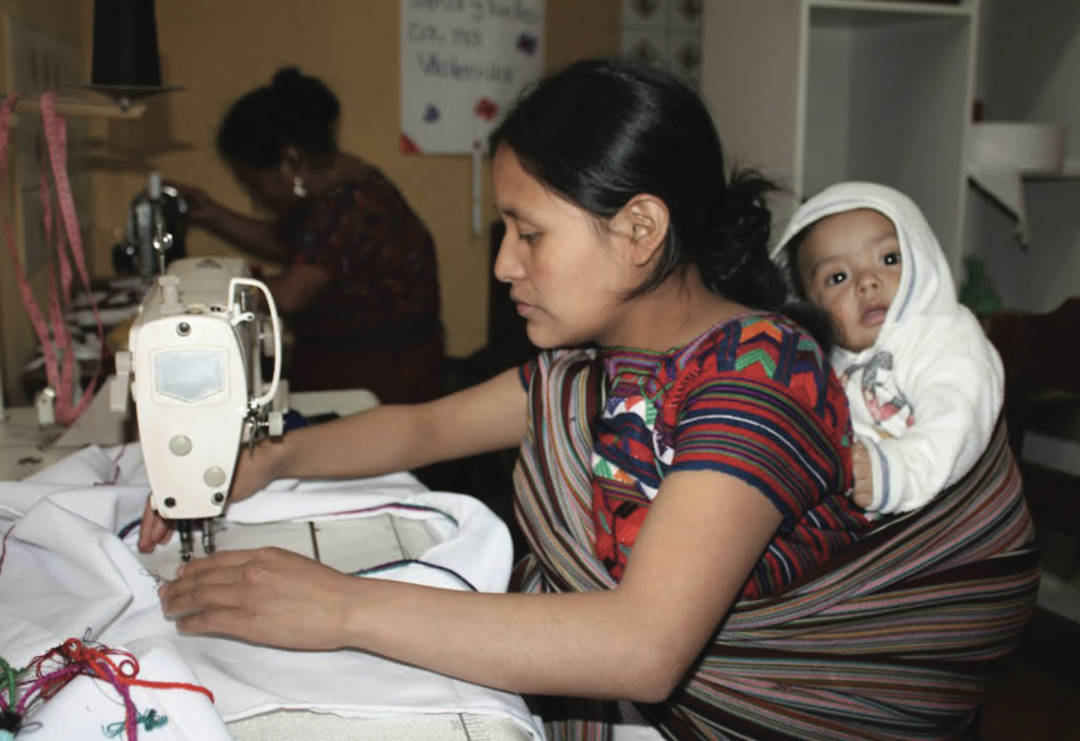 Woman sew while a baby is wrapped onto her back.