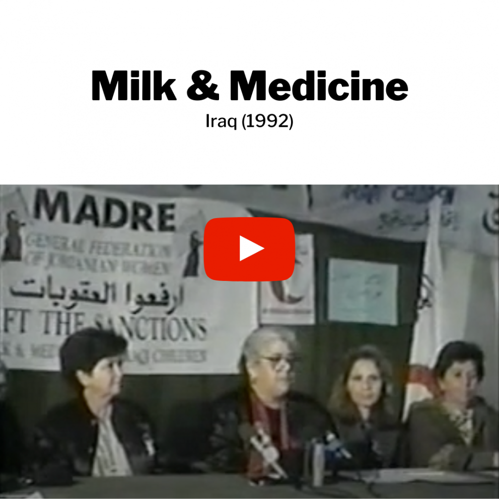 """Four women sit at a table for a conference event in front of a MADRE poster. Text above it reads: Milk & Medicine. Iraq (1992). There is a """"play"""" button to indicate that it can redirect to a full video."""