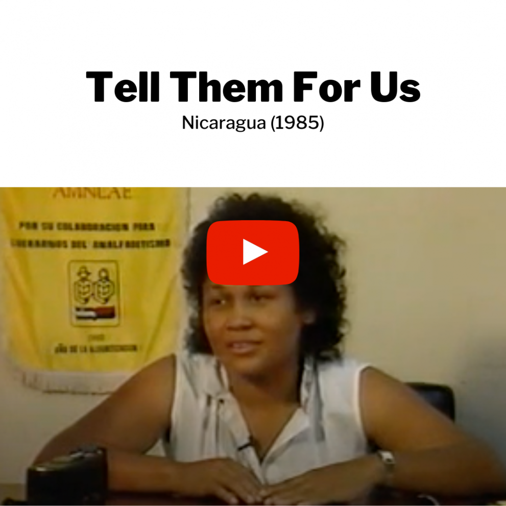 """Dr. Myrna Cunningham speaks to an audience while sitting at a table. Text above the image reads: Tell them for us. Nicaragua (1985). There is a """"play"""" button to indicate this image can redirect to a full video."""