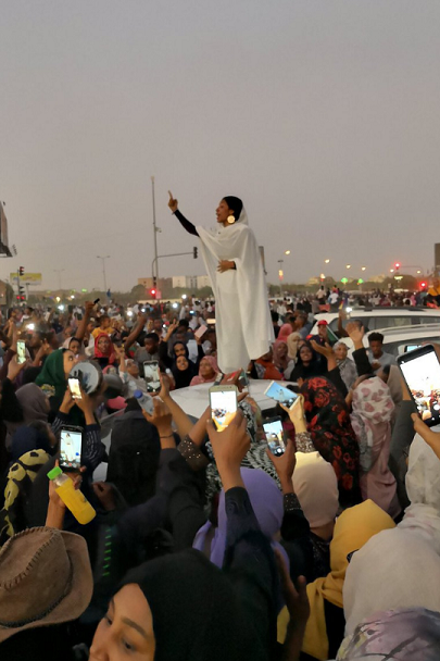 Woman protester dressed in all white leading the crowd in a chant while standing on top of a car.