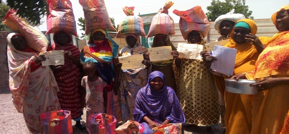 A group of women stand together after receiving sacks of seeds
