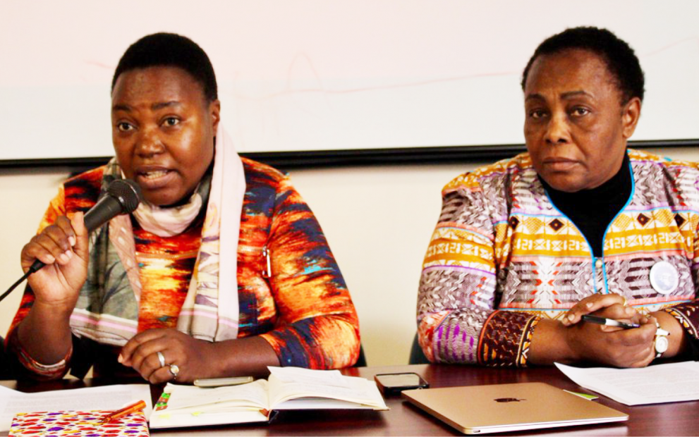 Zawadi Mambo speaking into a microphone during a panel event. She is sitting beside Julienne Lusenge, another member of our partner organization SOFEPADI.