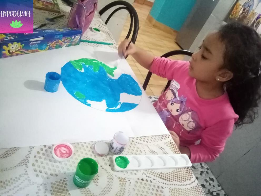 A young girl holds a painbrush while painting an image of a globe.