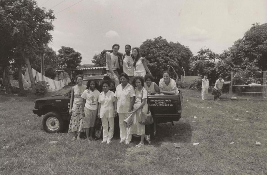 A group of women stand around and on top of a pick-up truck