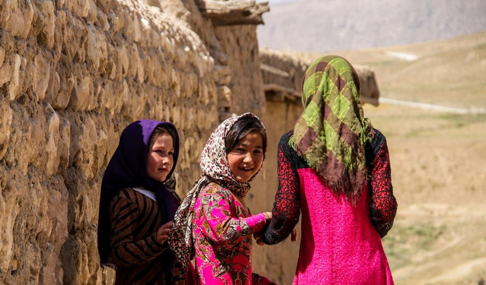 Three young Afghani girls walk together facing away from the camera. One young girl looks back at the camera and smiles.