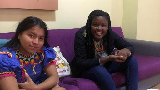 Monica and Laura sit on a purple couch, smiling into the camera and posing for a photo.