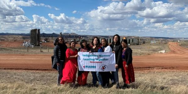 Indigenous women leaders posing together in front of an extraction zone