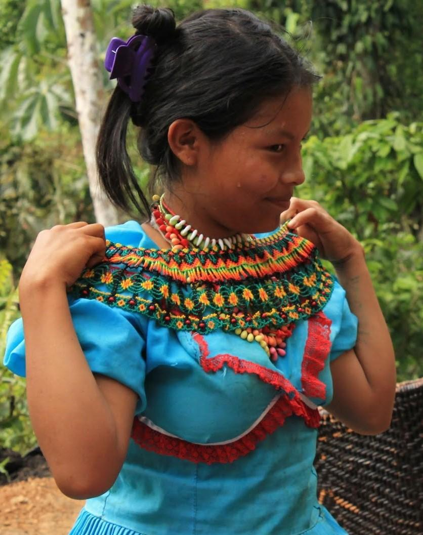 Monica is adjusting her traditional dress, which is a bright blue with red trimmings and a multi-color neckpiece.